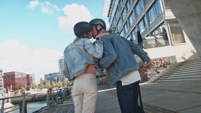 couple kissing while riding electric push scooters - monopattino elettrico video stock e b–roll