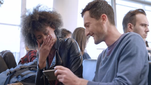 couple laughing while watching something on the smartphone while waiting for boarding at the airport - espressione del viso video stock e b–roll