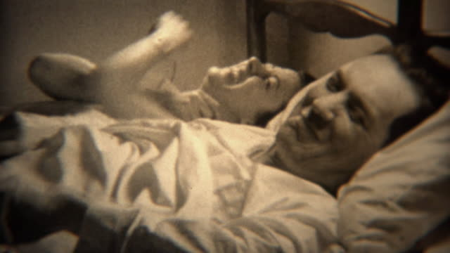 1937: Couple laying in bed together laugh at the scandal of their actions. . eyes closed videos stock videos & royalty-free footage