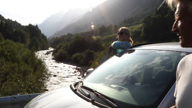 couple leave car, enjoy view up mountain creek - scendere video stock e b–roll