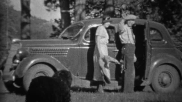 1935: Couple loading black dog into car in mountainous forest.