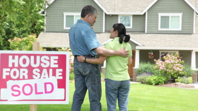 Couple look at new home, SOLD sign in foreground video