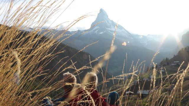 stockvideo's en b-roll-footage met paar uitkijken van ridge crest boven vallei, matterhorn verre - zermatt