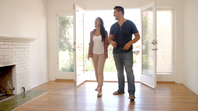couple looking around new home on moving day - proprietario d'immobili video stock e b–roll