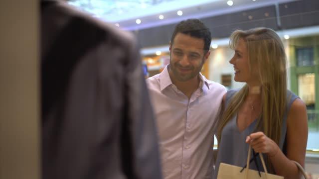 paar auf der suche an einem schaufenster und reden bereit, es zu kaufen - schaufenster stock-videos und b-roll-filmmaterial