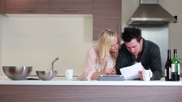 couple looking at bills in kitchen video