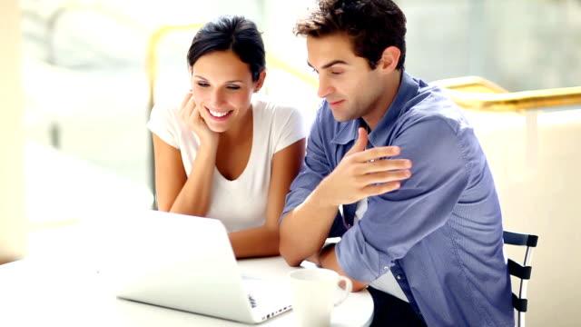 coppia cerca a vicenda mentre si utilizza il portatile in café - relazione umana video stock e b–roll