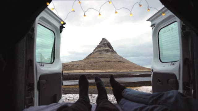 Couple looking at Kirkjufell mountain in Iceland from camper van Couple looking at Kirkjufell mountain in Iceland from camper van rv interior stock videos & royalty-free footage