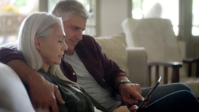 stockvideo's en b-roll-footage met paar kijken naar foto's in digitale tablet - een tablet gebruiken