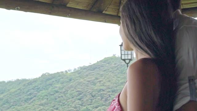paar mit blick auf die naturlandschaft von der hütte - lateinische schrift stock-videos und b-roll-filmmaterial