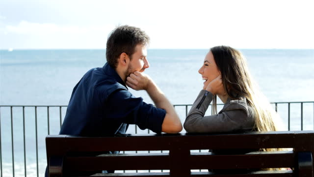 Couple looking each other on the beach Profile of a happy couple looking each other sitting on a bench on the beach falling in love stock videos & royalty-free footage