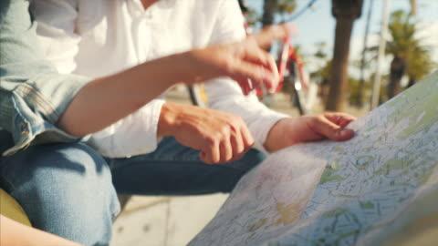 vídeos y material grabado en eventos de stock de pareja mirando el mapa de la ciudad. - turismo vacaciones