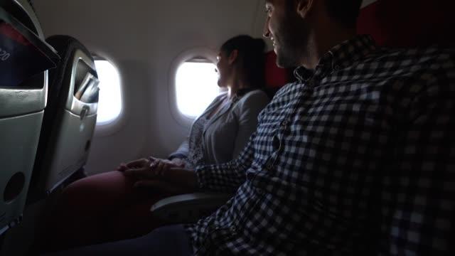 stockvideo's en b-roll-footage met paar kijken door raam van het vliegtuig - raam bezoek