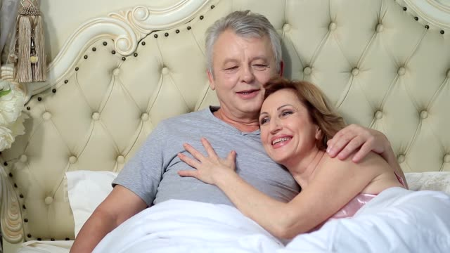 Couple lounging in bed after awaking cuddling video