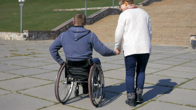 Couple lovers, Walk in park invalid on wheel chair and girlfriend video