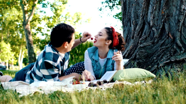 Couple lying on a blanket and feed each other with a cherry There are two people age 23. They are in relationship. He wear a shirt, and she wear a skirt, and white t-shirt. They are in picnic, and they enjoy it. cherry stock videos & royalty-free footage