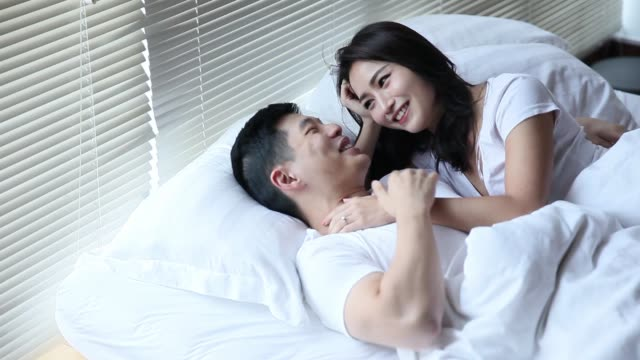 couple lying on bed talking to each other