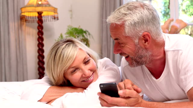 Couple lying on bed using smartphone together video