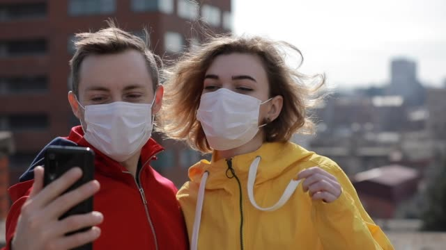 Couple make selfie in surgical masks on the city roof video