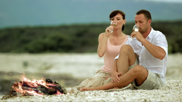 stockvideo's en b-roll-footage met slo mo couple making a toast on beach by fire - mid volwassen mannen