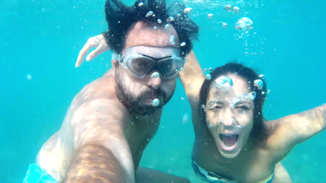 Couple making faces and waving underwater video