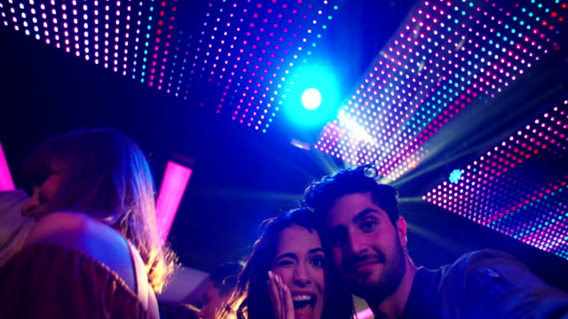 Couple making silly faces and posing for selfie in club video