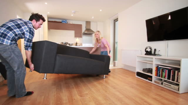 couple moving sofa in new home - möbel bildbanksvideor och videomaterial från bakom kulisserna