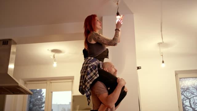 couple new home changing light bulb piggyback fun - винт стоковые видео и кадры b-roll