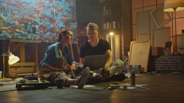 paar von künstlern sitzen in ihrem studio verwenden laptop-computer, arbeiten an einem projekt, sprechen und lächeln. malerund und ihr partner forschen. authentischer workshop mit ölgemälden und werkzeugen - künstlerischer beruf stock-videos und b-roll-filmmaterial