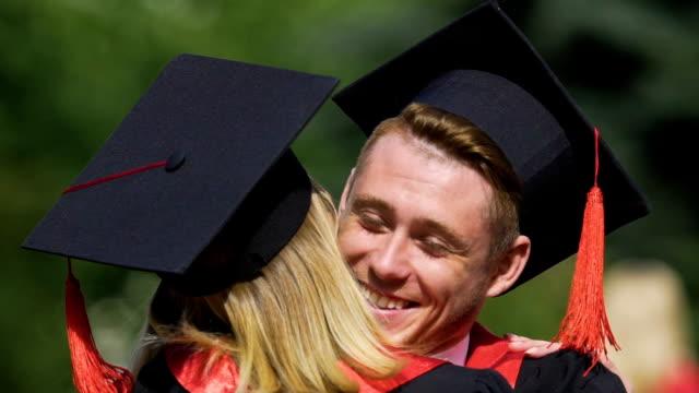 Couple of beautiful graduates smiling and hugging, enjoying moment, emotions video
