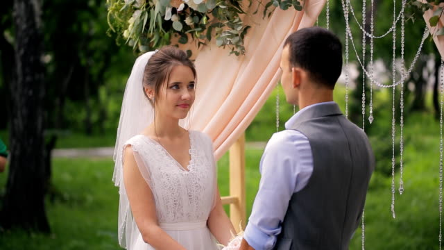 Couple of bride and groom near arch on wedding outdoor registration video