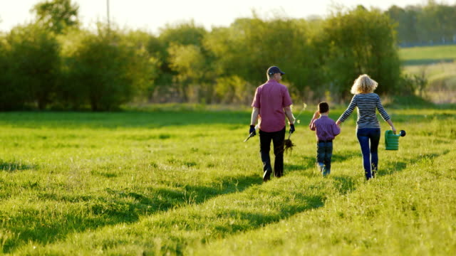 A couple of farmers are walking along a picturesque rural road. With them their little son. Go to plant a tree, carry a shovel and watering pad. Back view video