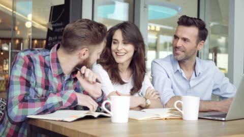 coppia di amici con laptop che pianificano nuovi affari al bar - abbigliamento casual video stock e b–roll