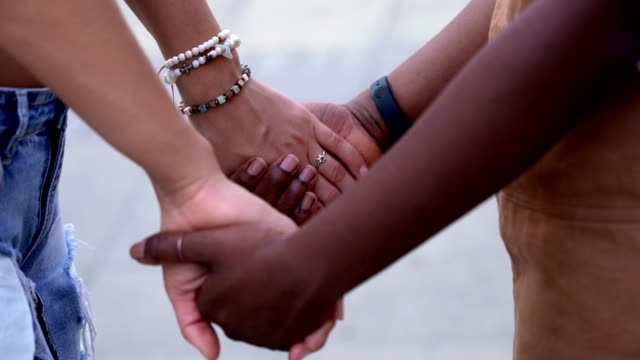 A Couple of Lesbians Holding Hands on the Street - Closeup shoot. A couple of lesbians holding hands on the street. Closeup shot of the hands. bisexuality stock videos & royalty-free footage