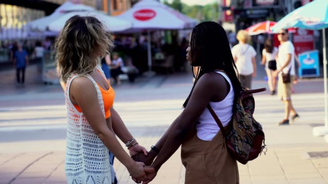 A Couple of Lesbians Holding Hands on the Street A couple of lesbians holding hands on the street while talking and laughing. bisexuality stock videos & royalty-free footage
