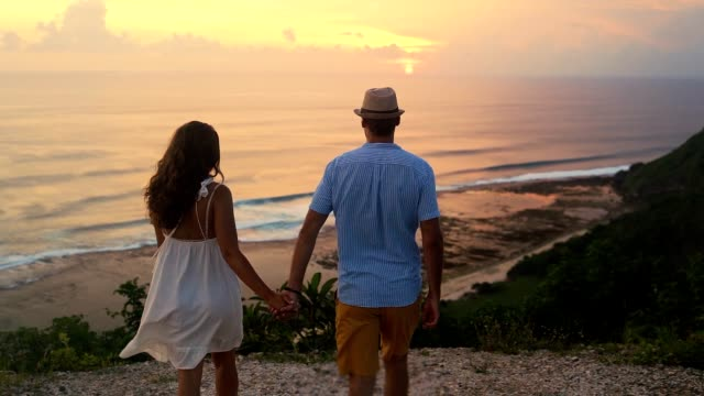 vídeos de stock e filmes b-roll de couple of lovers hand in hand go to cliff look at beautiful sunset, slow motion - bali