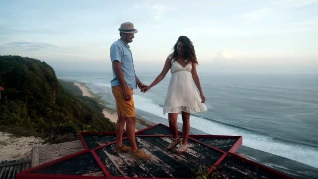 couple of lovers hugging, kissing and flirting, ocean on background, slow motion - young couple wedding friends video stock e b–roll