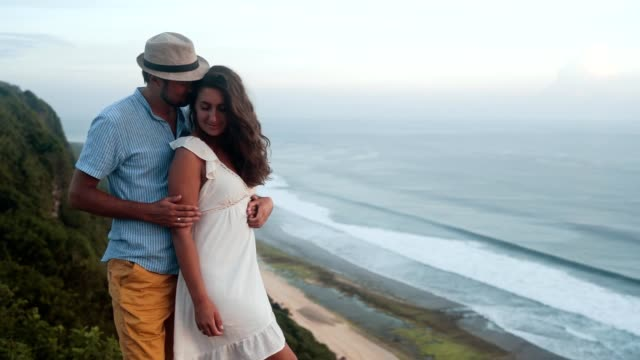 couple of lovers hugging, kissing and flirting on ocean background, slow motion - young couple wedding friends video stock e b–roll
