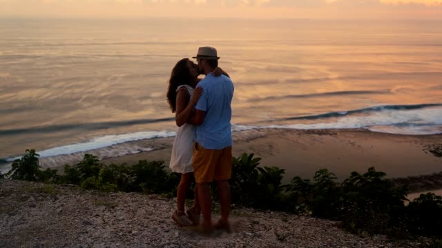 couple of lovers hugging, kissing on sunset and ocean background, slow motion - young couple wedding friends video stock e b–roll