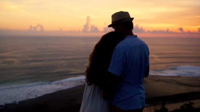 couple of lovers hugging, looking at beautiful sunset and ocean, slow motion - young couple wedding friends video stock e b–roll
