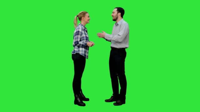 couple of lovers stand, talk, laugh on a green screen, chroma key - stare in piedi video stock e b–roll