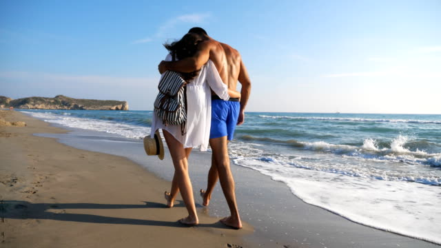 Couple of lovers walking at coast and hugging during recreation on resort. Man and woman strolling on beach and enjoying summer vacation together. Honeymoon of young pair. Concept of love or holiday.