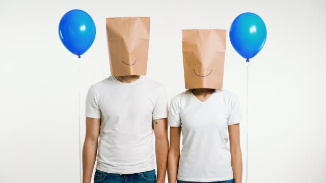 kafasına gülen kağıt torba lı bir çift hava balonları tutuyor - eksantrik stok videoları ve detay görüntü çekimi