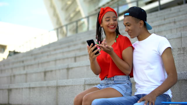 Couple of mixed-race teenagers sitting outdoor scrolling web pages on smartphone