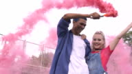 istock Couple of multiethnic teenagers having fun waving colored smoke bomb, hang out 1176097821