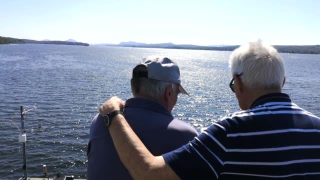 メンブレマゴグ湖で晴れた夏の日を楽しむシニア男性のカップル - 同性カップル点の映像素材/bロール