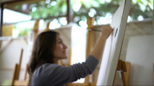 vídeos y material grabado en eventos de stock de pareja de estudiantes en la clase de arte dibujo sobre lienzo buscando feliz mientras dibujo - pintor artista