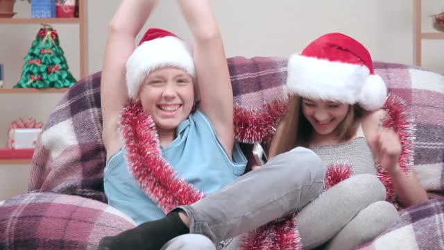 Couple of teenagers in Santa Claus hats, talking on speakerphone. video