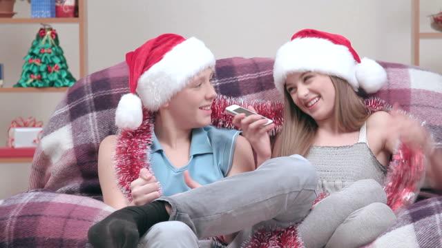 Couple of teenagers in Santa Claus hats talking speakerphone, smiling video