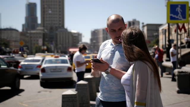 Un par de turistas llamando a un taxi usando un teléfono inteligente. Los turistas femeninos y masculinos están tratando de determinar la dirección que necesitan alcanzar. - vídeo